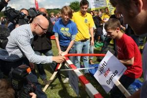 Schengen-Aktion in Krusau. Hauke Petersen bei der Zersägung des Grenzpfahls.